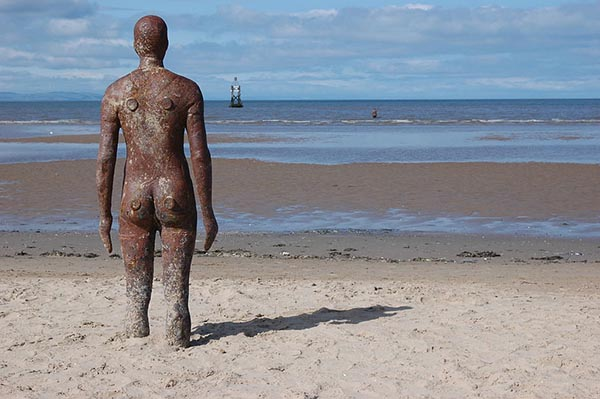 An iron sculpture of a human form, photographed from behind, stands on an ocean beach looking out to sea. Its legs are embedded in the sand, up to the knees. In the distance, just past the tide line, another figure stands in the water. There is a buoy further out in the water.