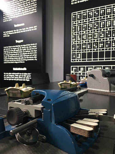 A bulky machine with a few keys sits on a large black table, with other supplies on it in the background, and a large informational poster about braille hangs on the wall behind it.