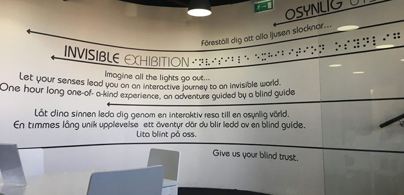 """The picture shows a white wall filled with text that is right as you come into the exhibition. It is an advertisement for the exhibition and prepares the visitor for their guided tour. It reads """"Imagine the lights go out... Let your senses lead you on an interactive journey to an invisible world. One hour long one-of-a-kind experience, an adventure guided by a blind guide... give us your blind trust."""""""