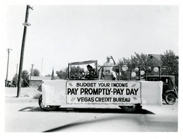 """A parade vehicle with a banner that reads """"Budget your income. Pay promptly-pay day. Vegas Credit Bureau."""""""