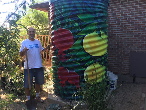 A man stands next to a large cistern painted with leaves and fruit. A brick building is behind the cistern.