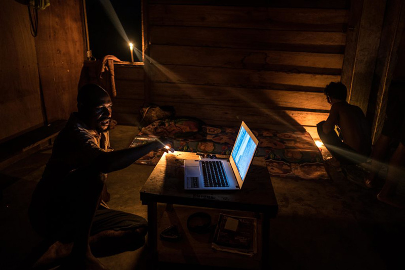 Photograph of a man using a laptop in a dark room.