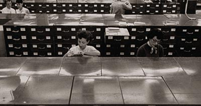 Historical photograph of women working at filing cabinets.
