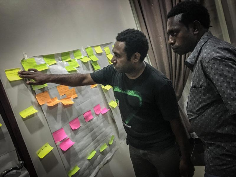 Two men looking at a board filled with sticky notes.