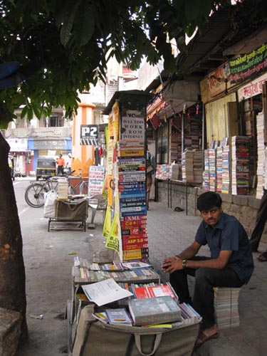A man sits by piles of books for sale on a sidewalk.