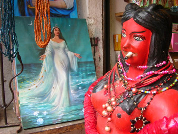 In the foreground is a sculpture of a red woman with black hair smoking a cigar. In the background is a painting of a woman in a long flowing dress.