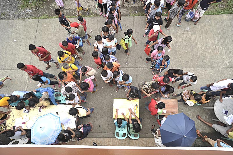 Photograph from above of people standing in queues in front of three tables.