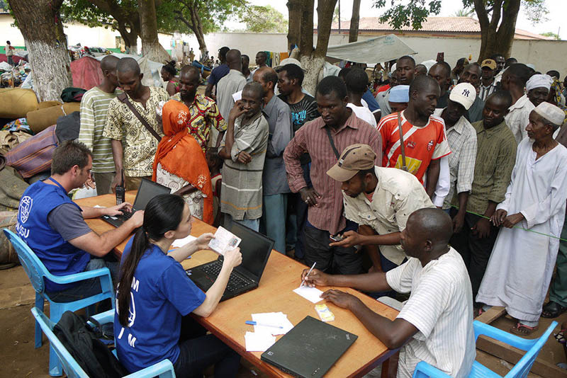 A white man and woman in blue t-shirts are seated at a table with laptops. A crowd of African people are standing in front of them. On the right, an African man is seated filling out paperwork.
