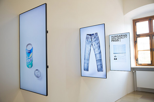 "Photograph of three photographs hung perpendicular to a white gallery wall. The photos are of a Sprite can, a pair of jeans, and a ""Hungarian High Quality Pass""."