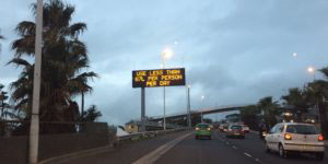 """Photograph of a highway with a sign above it reading """"Use less than 87L per person per day."""""""