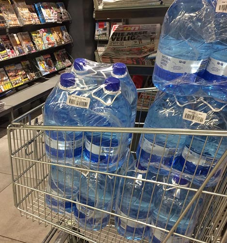 Photograph of a shopping cart overflowing with shrink wrapped large water bottles.
