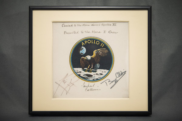 Photograph of a framed patch mounted on paper that has signatures on it.