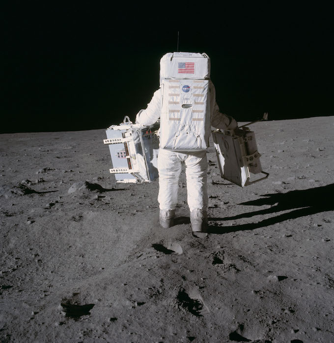 Photograph of Buzz Aldrin placing scientific instruments on the Moon.