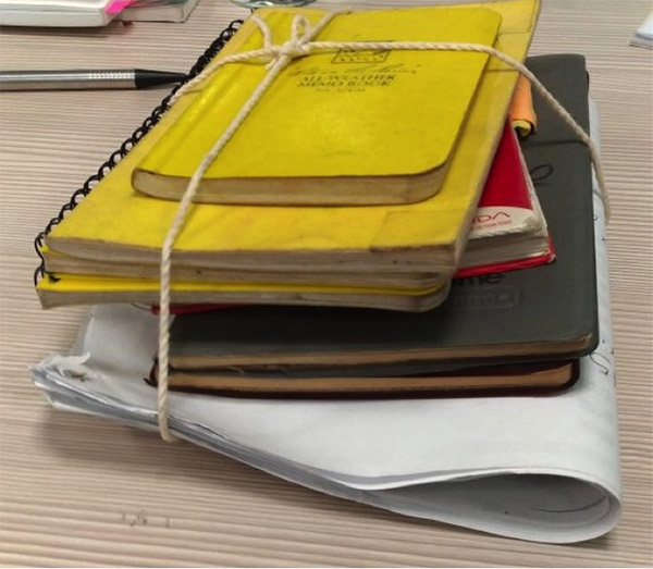 Photograph of yellow, red and grey journals tied together with twine along with folded paper.