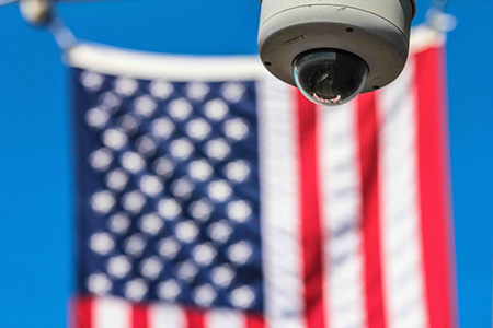 Photograph of a surveillance camera in focus. An American flag is hanging in the out of focus background.