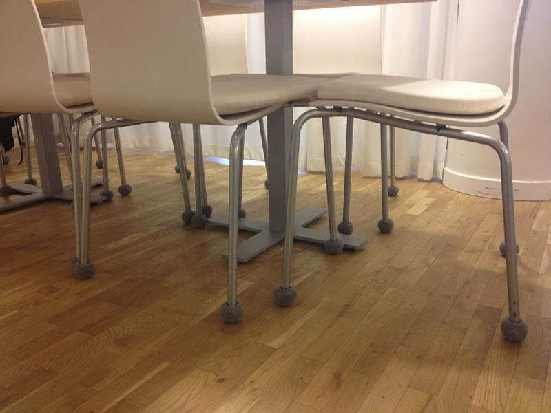 Grey tennis balls on chair legs in a kitchen