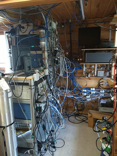 Photograph of a small room filled with equipment and wires.