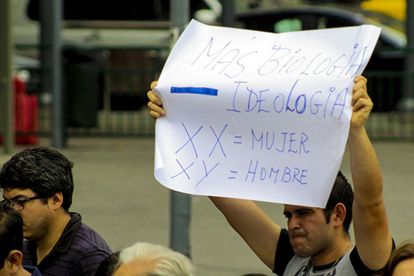 "An Evanglical protester holds a sign reading ""More biology, less ideology. XX = Woman, XY = Man at an anti-trans rally in January 2018"
