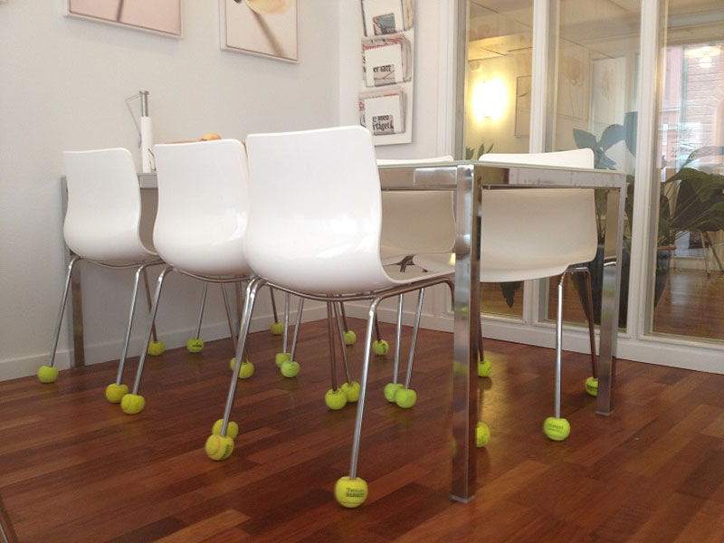 Yellow tennis balls on chair legs in a kitchen