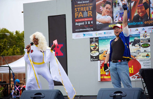 A drag queen in a Storm (X-Men) costume and a person in a Pokemon costume stand on a stage.