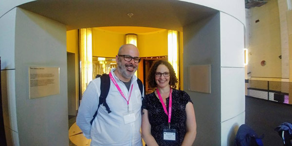 Photograph of two people posing for the camera and wearing pink conference badges.