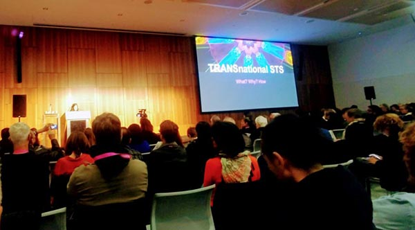 Photograph of a woman at a podium speaking before a audience. A projection screen shows a slide that saays TRANSnational STS: What? Why? How