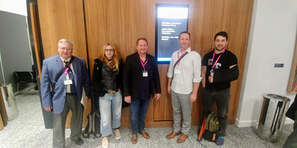 A photograph of five people wearing pink conference badges posing for the photo.