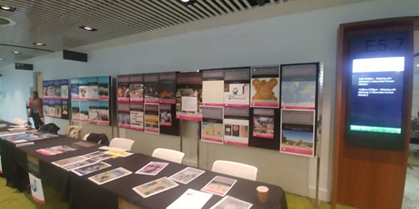 Photograph of a wall display of images with a long table with more images on it in front of it.