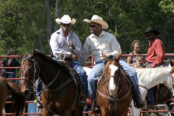 Photograph of men in Stetson style hats, white shirts and blue pants on horse back. More people and horses can be seen in the background.