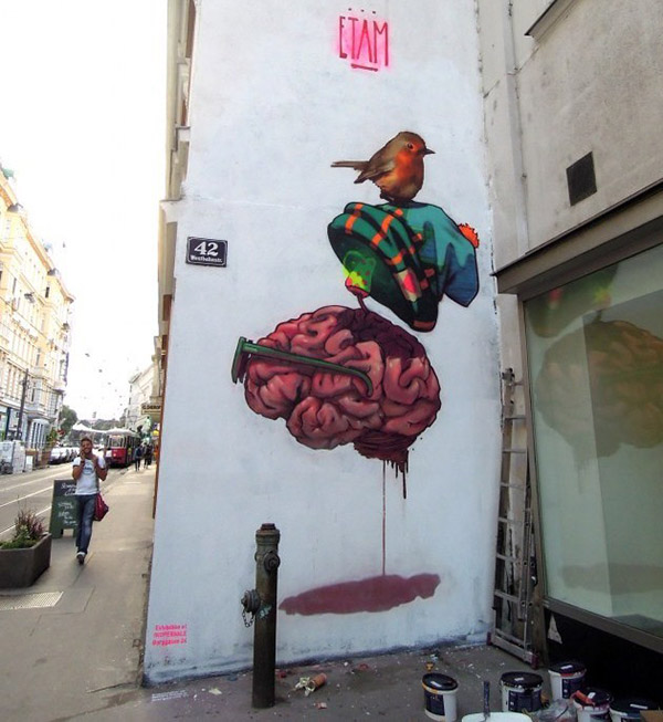 Photograph of a mural on a white building. The artwork is a bird standing on a beanie hat hovering above a brain wearing glasses.