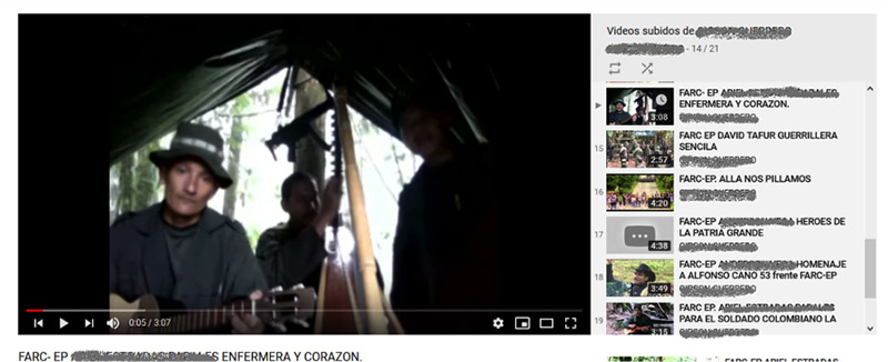 A screen capture of a YouTube video of Farc music. The still shows a man a gray shirt and gray broad rimmed hat, in a tent, and one other person the background.