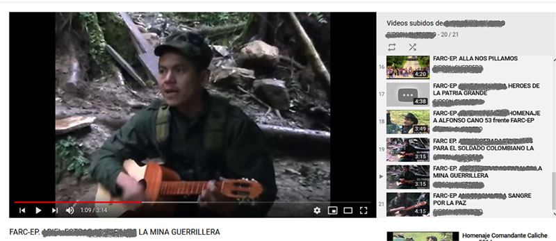 A screen capture of a FARC YouTube channel. The still shows a man dressed in green fatigues playing an acoustic guitar.