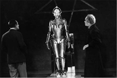 Black and white still. Two men in suits face a chrome female robot figure.