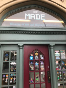"Photograph of a front door with the windows covered in stickers. Above the door a window has the sign ""The Made: Museum of Art and Digital Entertainment"""