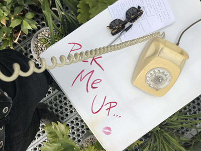"""Photograph of a vintage yellow dial phone sitting on top of a white table that says """"Pick me up..."""" on it with a lipstick kiss mark below it."""