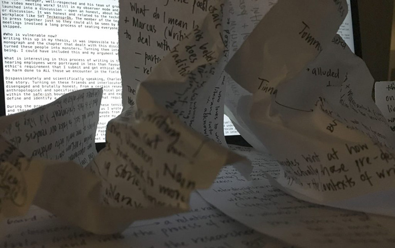 The image shows crumpled paper in the foreground and a computer screen with a text file open in the background. The paper in the foreground is scribbled full of notes - the discarded drafts of earlier versions of the article I was struggling to write. The text on the computer screen is of the umpteenth draft of the same article - no easier to write on a computer than it was with pen and paper.
