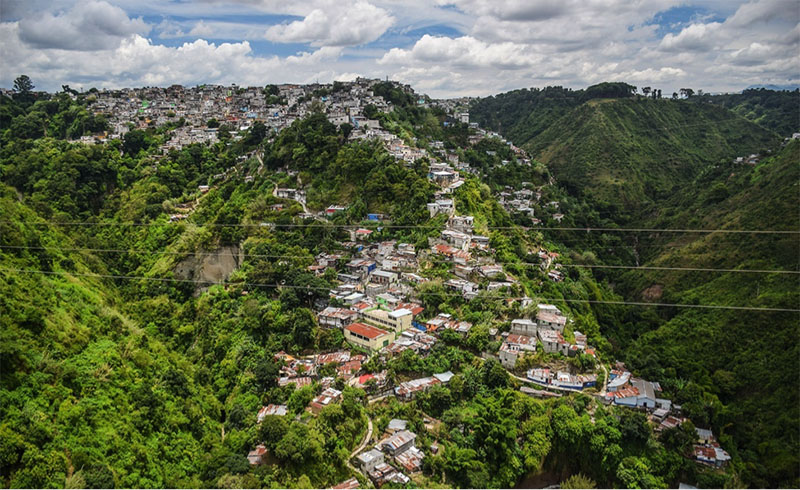 The picture shows a lush, green ravine/valley full of terra cotta roofed houses in Guatemala City's Zone 3