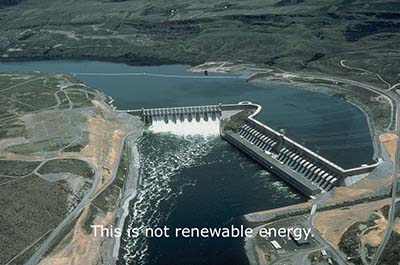 """This image is an aerial view of a large hydropower dam. The upper half depicts the reservoir, the lower half shows the water gushing through the dam. It is captioned, in the lower half, with the phrase """"this is not renewable energy."""""""