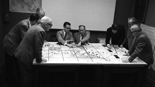 A group of white men meet around a table in a black and white photo. They are playing what looks to be a board game.