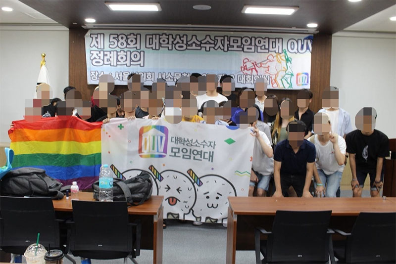 Photograph of a large group of people holding up banners and a rainbow flag. Their faces have been digitally obscured.