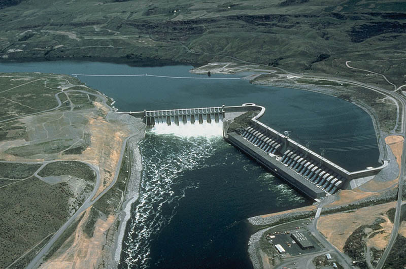 This image is an aerial view of a large hydropower dam. The upper half depicts the reservoir, the lower half shows the water gushing through the dam.