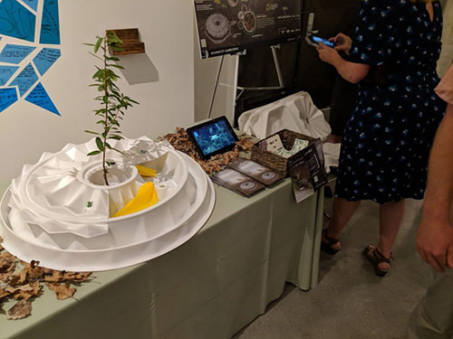 A table with a light colored table cloth shows two examples of biomimicry. In one example, we can see a tablet screen nestled among natural detritus. In the other, we can see a green sapling growing out of a white structure.