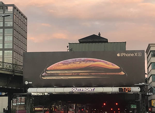 Photograph of a billboard for the iPhone with sunset sky and city in the background.