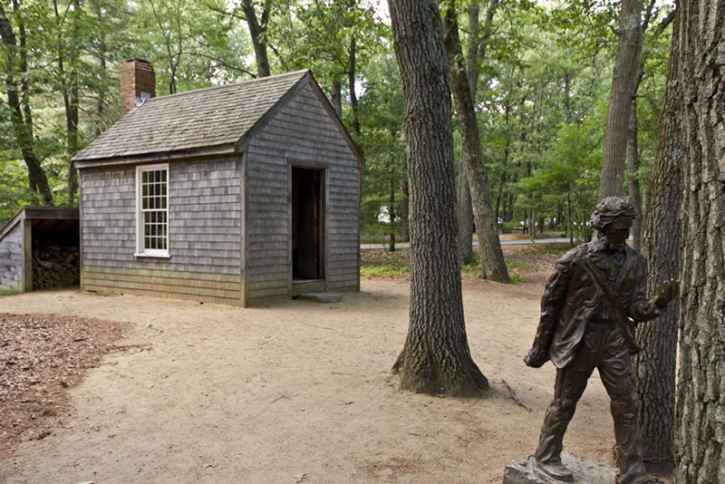 A small replica of Thoreau's cabin and statue near Walden Pond can be seen against a backdrop of green trees. The house is small, grey, one-room building with a red brick chimney. The statue is brownish in color, perhaps made of bronze.