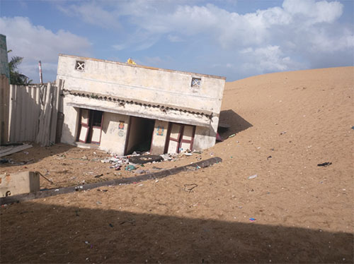 A whitewashed concrete building sinking into sand.