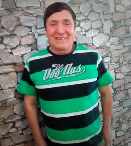"A stocky man in his 60's looks into the camera. He has short, brown hair swept to the right and olive skin. He is wearing a T-shirt with large green and black stripes interspersed with white stripes. The T-shirt reads ""Doo Aus."" Behind him is a stone wall filling the entire background of the photo."