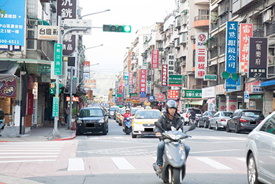 The image depicts taiwanese traffic, with a motorist in the foreground and cars in the background. Also in the background are buildings full of billboards, streetlights. The image conveys a general sense of both bustling street noise and crowded living/business quarters.