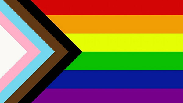 A rainbow flag (top to bottom red, orange, yellow, green, dark blue, and purple) is shown with 5 color chevron pattern coming from the left side, featuring black, brown, light blue, light pink, and white stripes.
