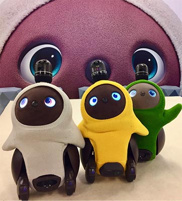 Three cute, brown robots in different colored robes that frame their round heads.