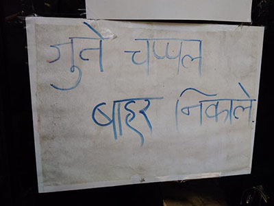 """A sign written in Hindi reads """"please leave your shoes outside."""""""